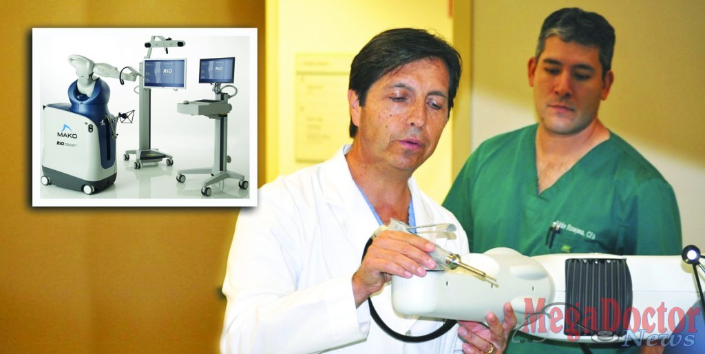 "Dr. Raul Marquez, Orthopedic Surgeon demonstrates a robotic arm called ""RIO® the Robot"", and to his left is Eddie Hinojosa."