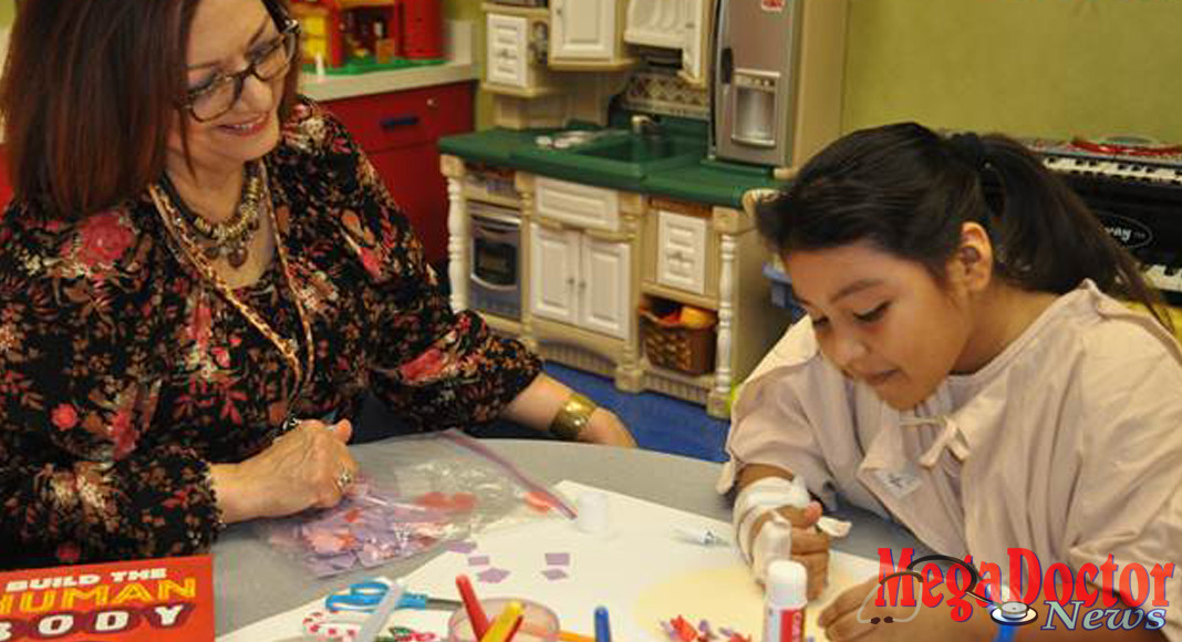 Maricela Medina, CCIS, Child Life Specialist at Valley Baptist Medical Center-Harlingen, leads 9-year-old Stephanie in an arts and crafts activity during her stay at the hospital.