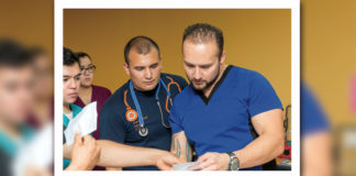 John García (at right), a UTRGV pre-med biology major and president of the Premedical Biomedical Society, and Gabriel Yáñez (at left), a UTRGV graduate biology student, are seen reviewing patient information at the Culture of Life Ministries nonprofit clinic in Harlingen. In all, 21 UTRGV undergraduate pre-med students are volunteering, under supervision, at the ministry, which has provided free medical services to community members in need, for more than a year. (Photo by David Pike)