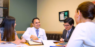 Pictured Above: Dr. Michael Martinez, Bariatric Surgeon at the DHR Health Bariatric and Metabolic Institute, speaks with a patient. Dr. Martinez received the Young Physician of the Year Award from the National Hispanic Medical Association.