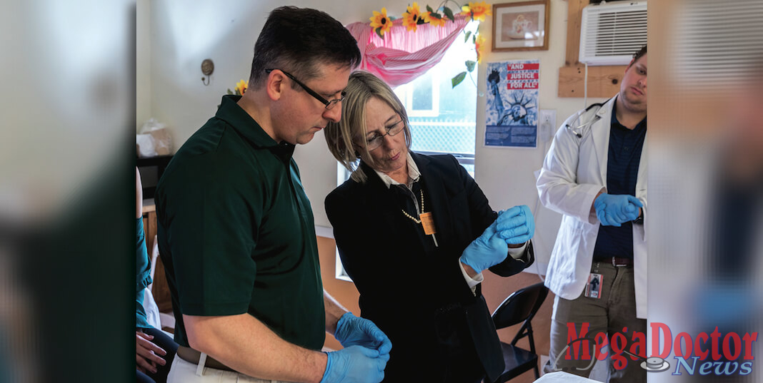 Linda Nelson, senior director of Clinical Operations for the UTRGV School of Medicine, instructs first year medical student Richard Wagner on how to prepare a flu vaccine. More than a dozen first and second year medical students, under the supervision of School of Medicine faculty and staff, administered flu shots to patients at the Indian Hills community. (UTRGV photo by David Pike)