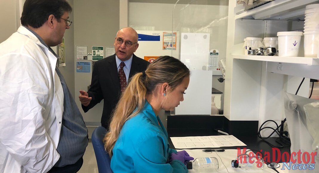 "Dr. Christopher Vitek (at left), UTRGV associate professor of biology, and state Rep. R. D. ""Bobby"" Guerra (center), spoke this week in the Zika research lab on the Edinburg Campus, as  biology graduate student and lab manager Heather Hernandez performed tests on pesticide effectiveness. Guerra and other guests toured the facility and got updates on important research UTRGV is conducting on Zika and other vector-borne diseases. (UTRGV Photo by Victoria Brito)"
