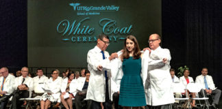 Dr. Leonel Vela and Dr. John Krouse form The University of Texas Rio Grande Valley School of Medicine welcomed its newest students with a White Coat Ceremony on Saturday, July 28, 2018, at the Performing Arts Center of the Harlingen Consolidated Independent School District. Marking the beginning of their education and career, the new medical students received their signature white lab coats from School of Medicine leaders, then recited the Hippocratic Oath – which acknowledges their primary role as caregivers – in the presence of their loved ones, school leaders, and peers. Dr. John H. Krouse, executive vice president for Health Affairs and dean of the UTRGV School of Medicine, congratulated the students for their achievements thus far and emphasized the importance of staying humble and showing compassion. (UTRGV Photo by David Pike)